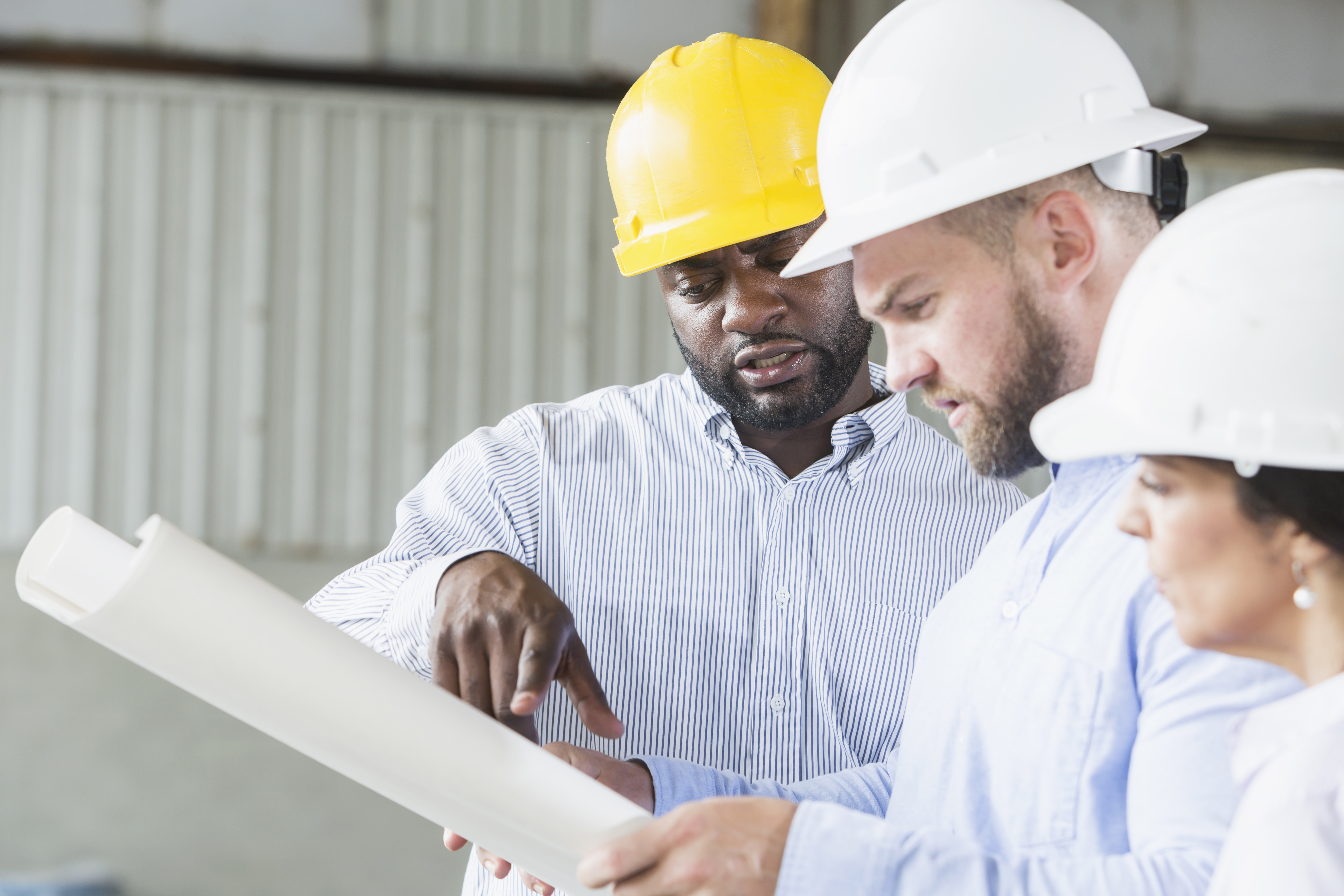 Three multi-ethnic workers wearing hardhats, looking at plans. The focus is on the African American man wearing a yellow hardhat.