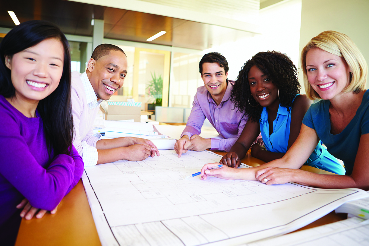 Group Of Architects Discussing Plans In Modern Office Smiling At Camera