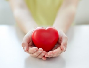 46140249 - people, love, charity and family concept - close up of child hands holding red heart shape at home