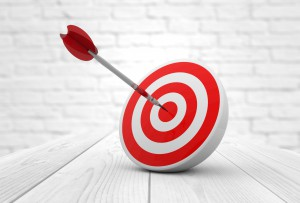 45968866 - strategic business solutions or corporate strategy concept: digital generated dart in the center of a red target, modern wooden and bricks background.